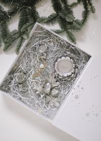 Новогодняя подарочная коробка украшена серебристыми снежинками с набором елочных украшений фото